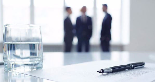 Contract, pen and glass of water while in the background men talking.