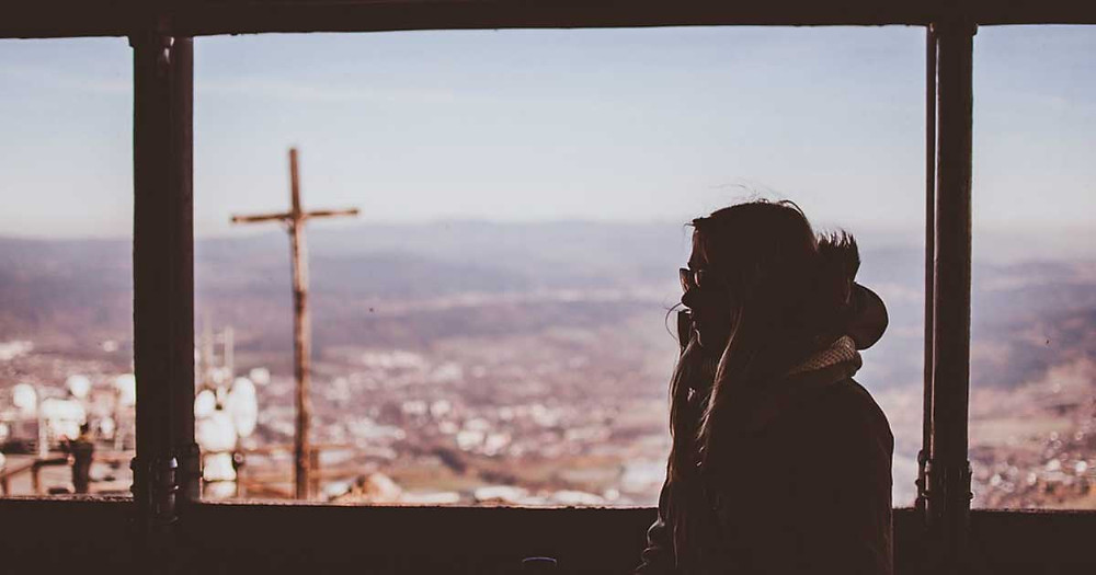 Woman reflecting on her life with a cross in background