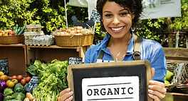 Woman in produce section holding an organic sign.