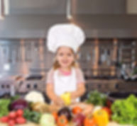 Little girl with chef hat and cutting board.