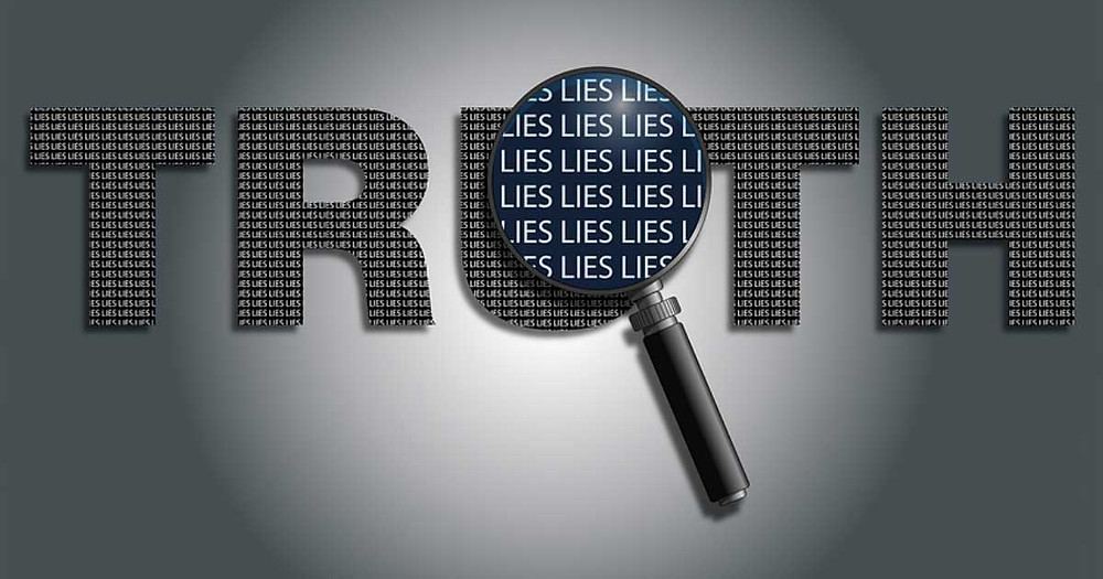 Magnifying glass hovering over the word truth and finding it is made up of the word lies in very deceiving print.
