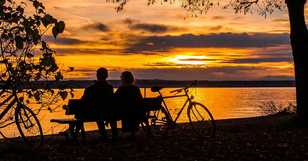 Couple relaxing after bike ride next to a lake and sunset.