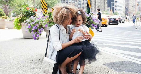 A woman fussing with her daughter on a city street in motherly way.