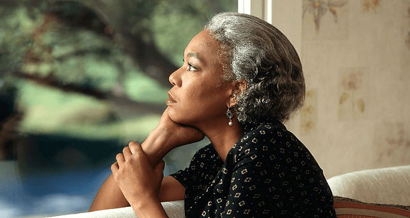 Older woman looking out a window with a wounded and sad look on her face.