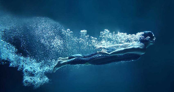 Water, Your Most Vital Nutrient. Girl diving through the blue water, bubbles streaming behind her.