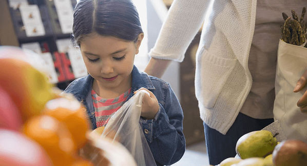 Little girl placing organic food in a shopping bag for her mother. Why Organic Food.