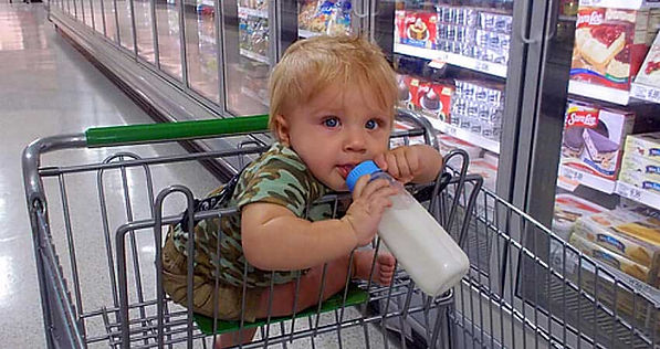 Little boy in a shopping cart with dark circles shadowing their beautiful eyes.