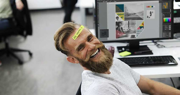 Man at his work desk, laughing with a sign on his head that reads be happy.