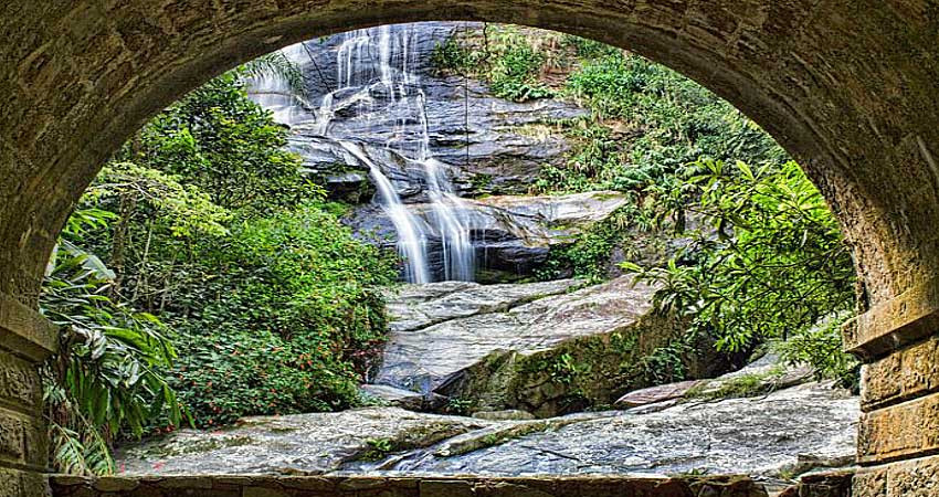 On the leading edge, edge of a path with a waterfall and beautiful landscaping.