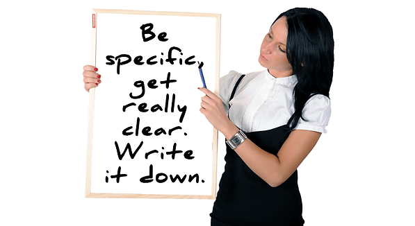 Woman and a white board that reads, Be specific, get really clear. Write it down.