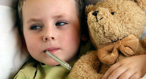 Boy, thermometer and his teddy bear. Down with the flu.