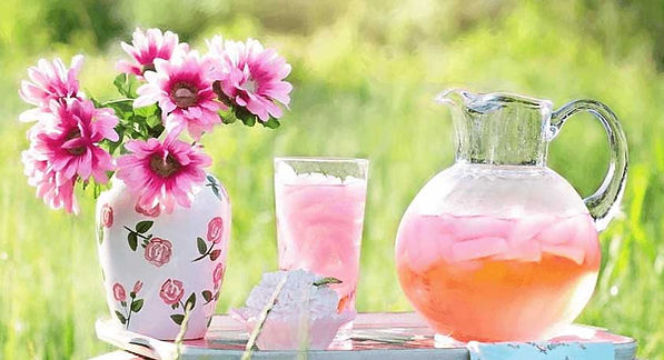 Juice pitcher of Amazing Cranberry & Lemonade juice on a beautiful decorated table and flowers.
