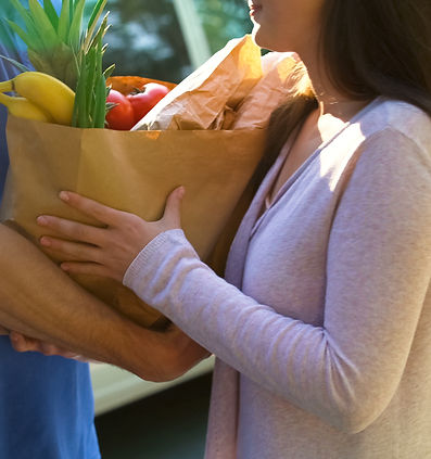 Smiling woman receiving grocery bag from