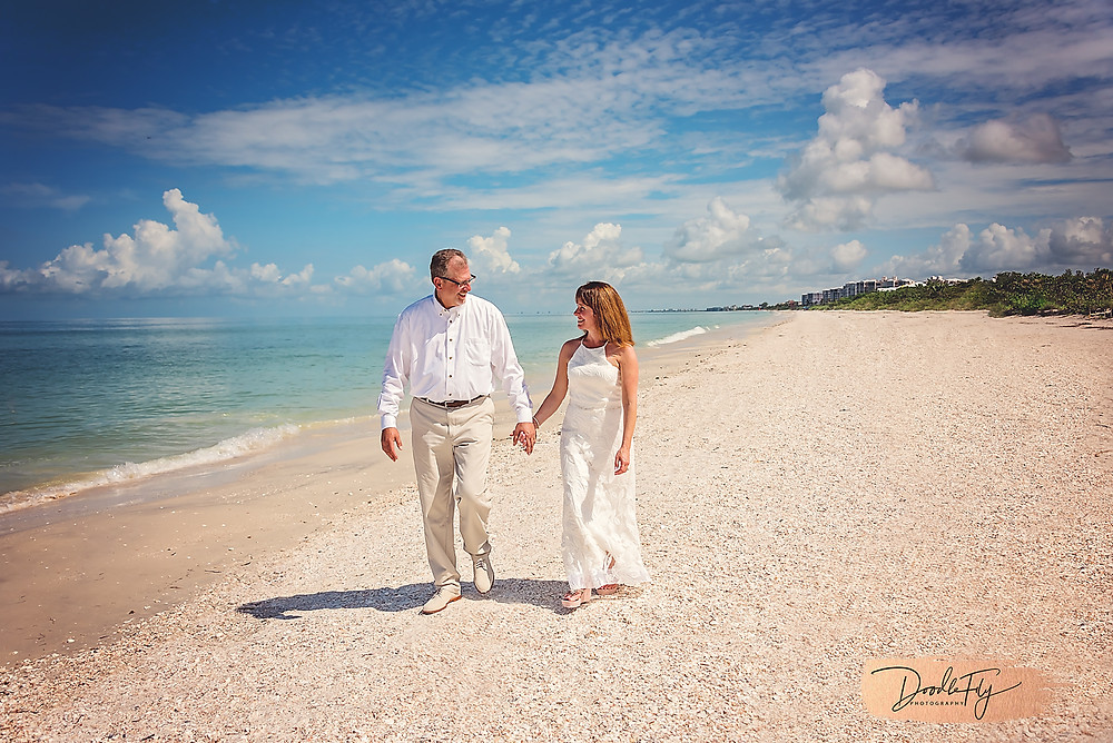 Bride  and Groom walk on the beach, barefoot Beach, Naples Florida photo by Doodle Fly Photography