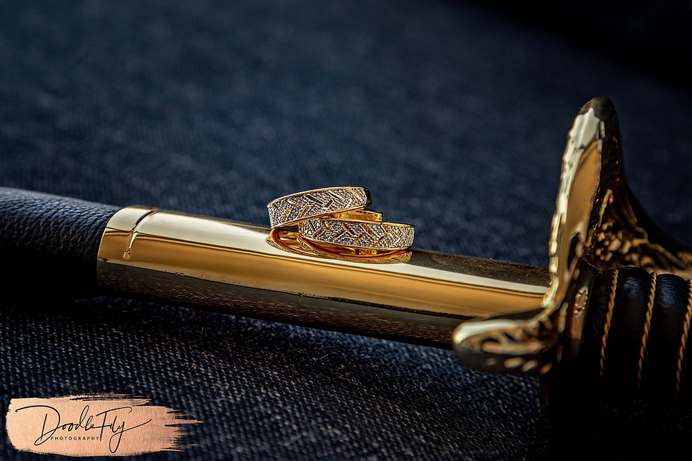 Doodle FLy Photography wedding photo of Wedding Rings Details with Navy Saber Sword for Bride and groom at Burroughs Home Venue in Fort Myers Florida