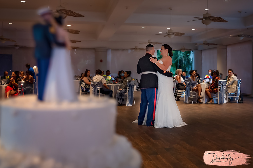 Doodle FLy Photography wedding photo of bride and groom dancing and wedding cake in foreground during first dance at Burroughs Home Venue in Fort Myers Florida
