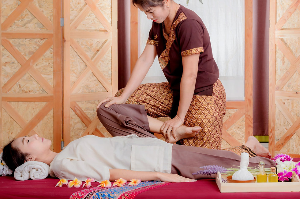 Thai Masseuse doing massage for woman in