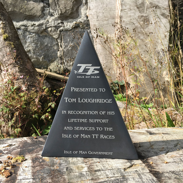 Isle of Man TT Award in honed Pooil Vaaish black limestone 3cm thick, cut to triangular shape and etched with logo and text.