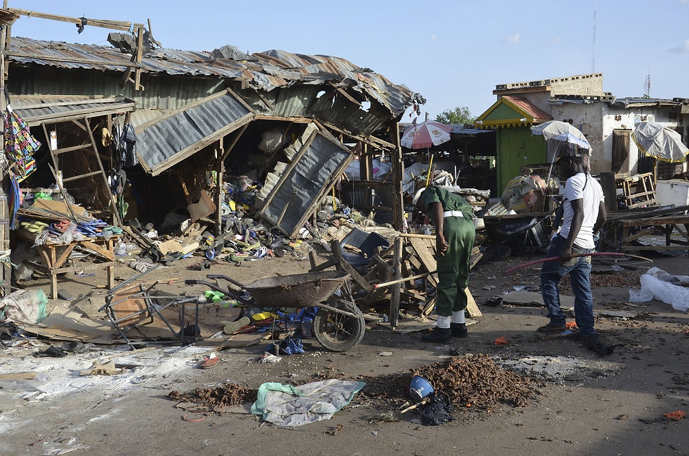 People gather at the site of a suicide bomb attack at a market in June 2015 in Maiduguri, Nigeria, where two girls blew themselves up near a crowded mosque. Jossy Ola/AP