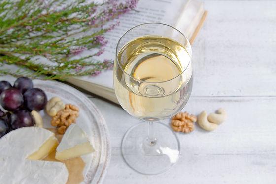 A glass of white wine, grapes, purple fl
