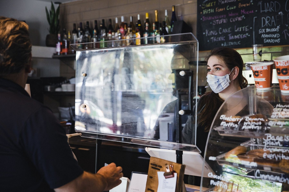 A barista wears a protective mask and stands behind a plastic shield in reopened Woodstock, Georgia