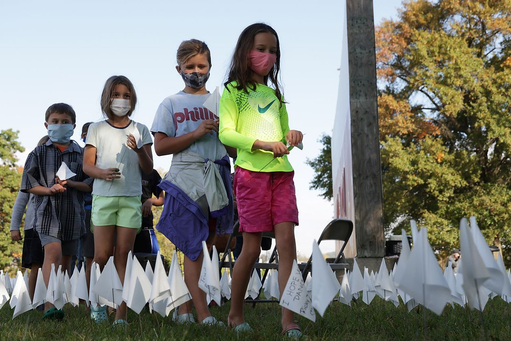 Children plant 240,000 flags on Friday in Washington DC to memorialize Americans killed by SARS-CoV-2