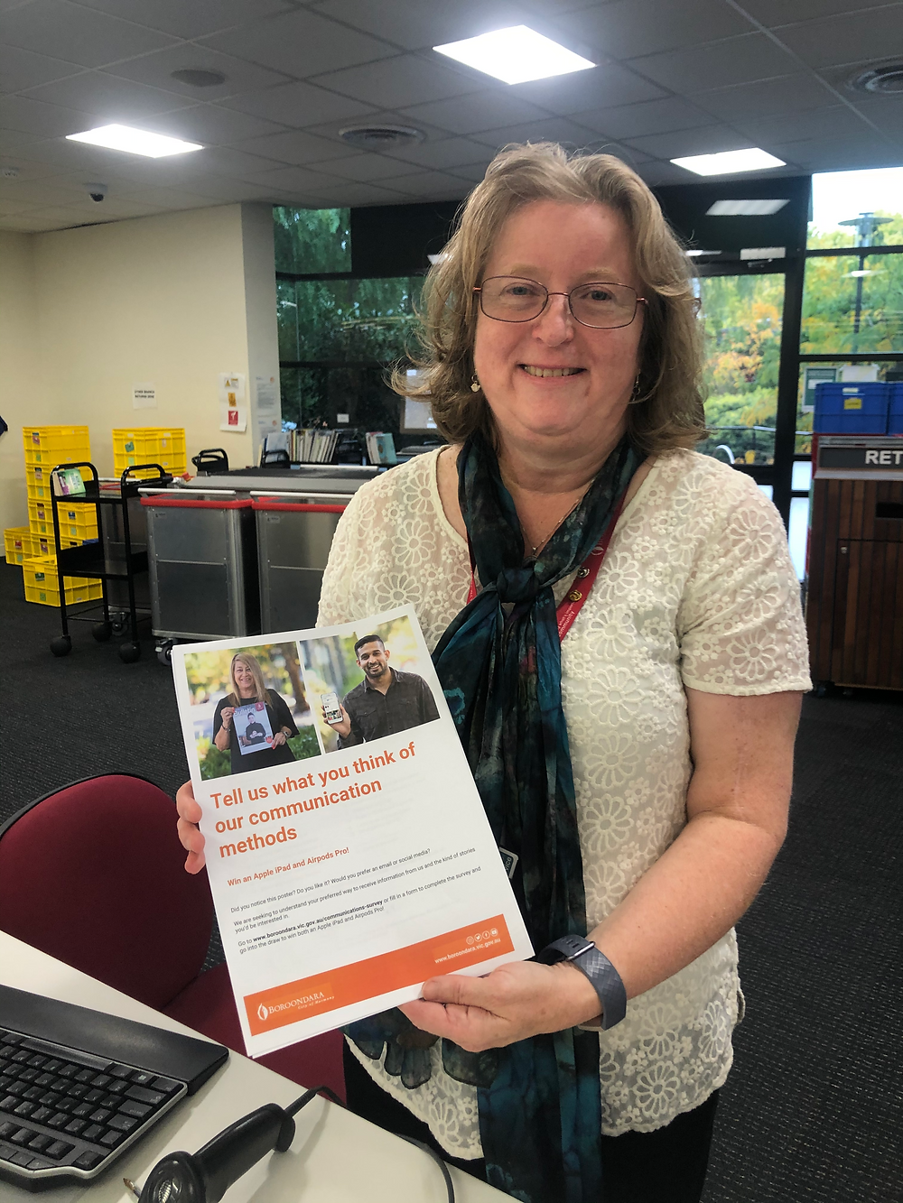Cheryl at the Hawthorn Library, holding up the print version of the Communications Evaluation Survey at the front desk and smiling.