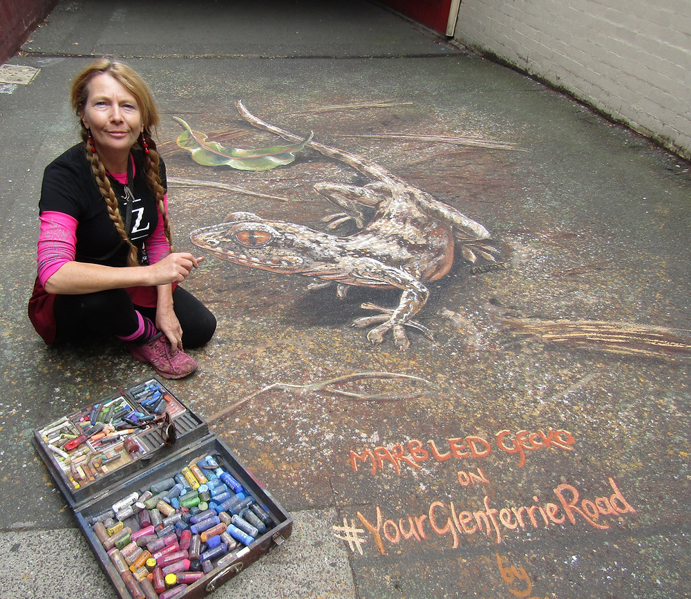 """Artist Ulla Taylor crouches next to her chalk art done for 'Chalk the Walk' in the railway arcade at Glenferrie Station, a life-like gecko illustration with """"Marbled Gecko on #YourGlenferrieRoad"""" written underneath."""