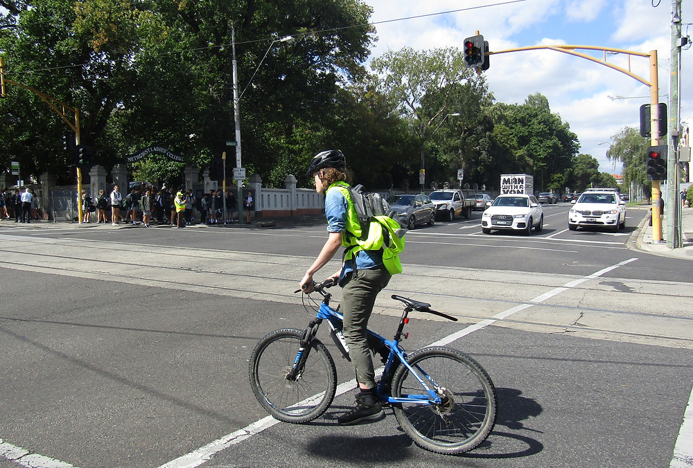 A young cyclist wearing a high-vis shirt, helmet, and backpack cycles through the Glenferrie Road intersection in front of Methodist Ladies College, Hawthorn.