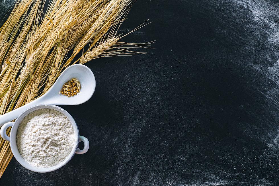 wheat-ears-and-wheat-flour-on-black-back
