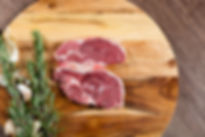 Raw lamb chump slices on chopping board