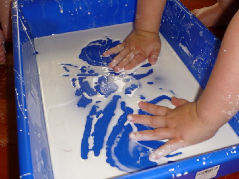 Child experiencing cornflour and water in shallow tray