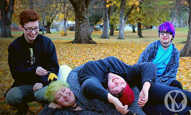 A group of Odyssey youth in a pile of leaves in a park setting.