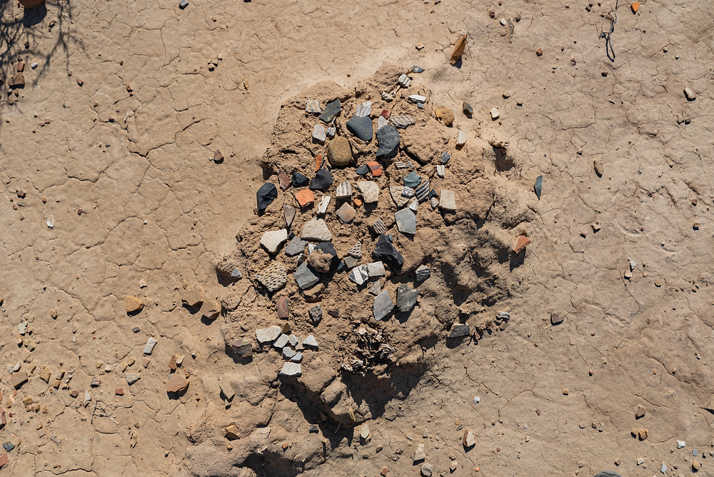 Ancient pottery shards on a dusty dirt mound.