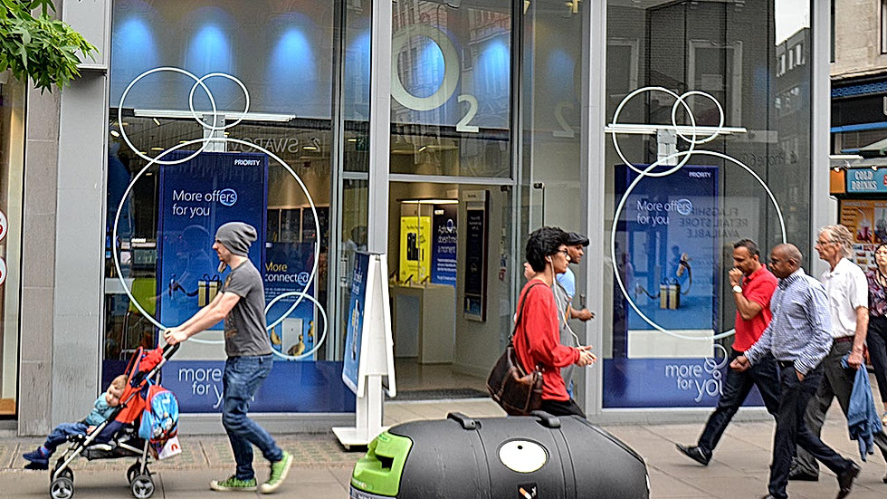 Shoppers walking past o2 high street window front