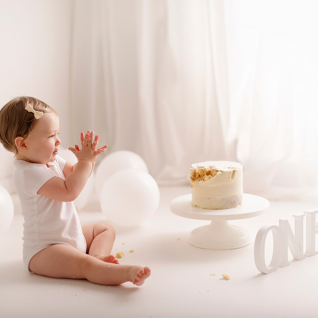 baby girl cake smash  4 bubbles on face.