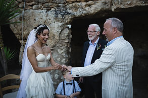 Me putting a ring on my husbands finger at our own ceremony in Italy, outside a cave. Our friend officiating  & my friend's son holding the other ring.