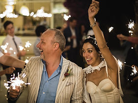 Our wedding reception, late evening. Big grins as we walk through an archway of our friends holding sparklers