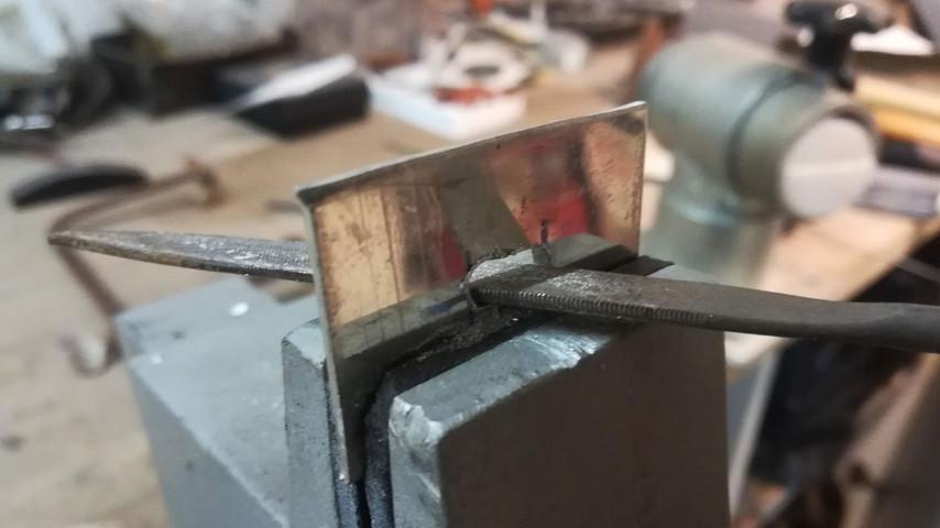 Hullet i tinpladen tilpasses så det passer med tykkelsen og bredden på anglen.