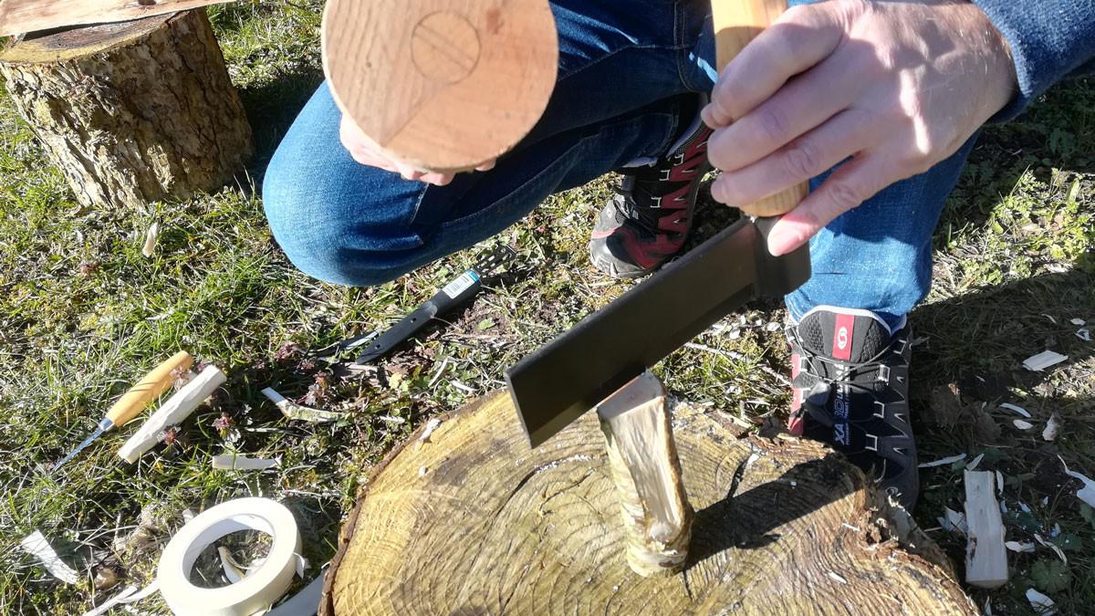 Med kløvejernet flækker jeg siderne af grenen så den bliver mere trekantet. Så er der ikke så meget at snitte væk senere. Man kan også bare bruge en økse.