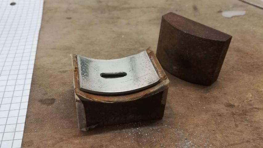 Jeg har en lille stålklods, eller matrice, hvor der er en indvendig og en udvendig diameter på Ø75 mm. Her kan jeg lægge metalpladen i og så banke dem sammen. Derved får metalpladen den runding der passer til indlæggene... Det er mega smart og meget nemt. Man kan selv lave en i en hård træsort - det virker lige så godt.