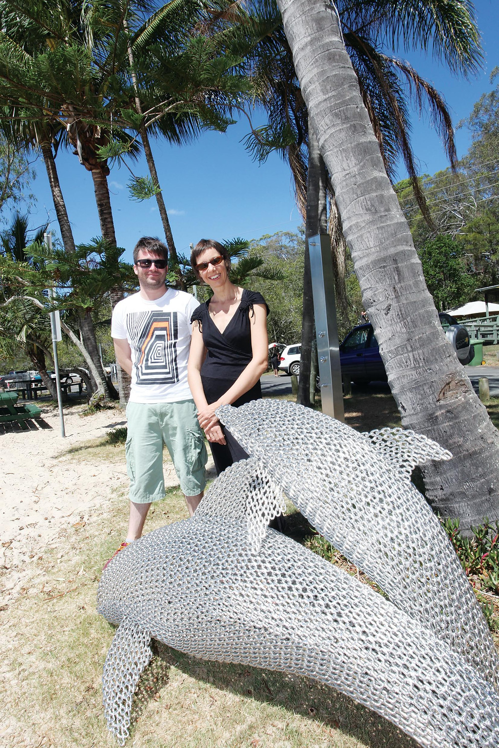 Girt by Sea judges Ruth McDougall and Peter McKay with the popular 'dolphins' sculpture on Karragarra beach.