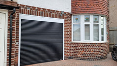 Securoll compact roller door in black with white guides and box