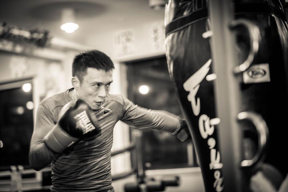 Chinese boxer punching heavy bag
