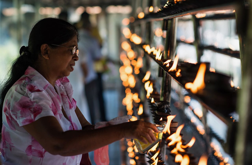 Sri Lankan elderly lady lighting candles at a temple