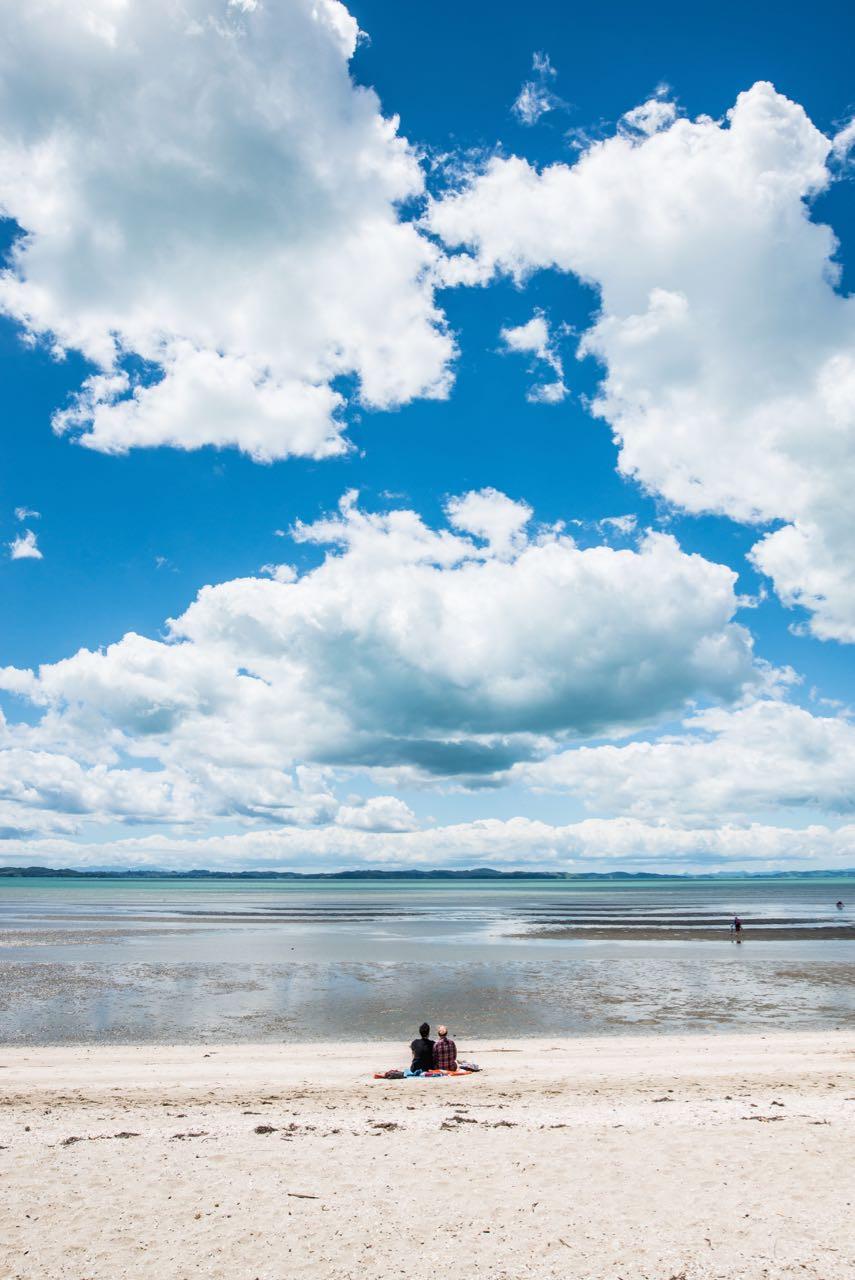 Couple enjoying the afternoon sun. Eastern Beach, Auckland