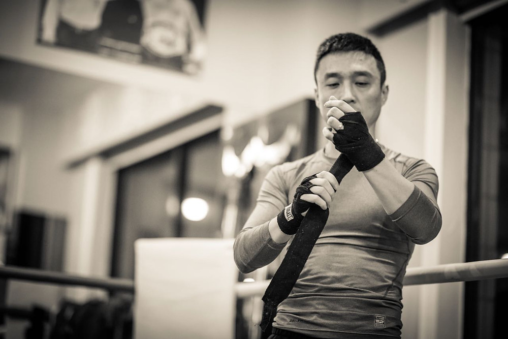 Chinese boxer putting on hand wraps