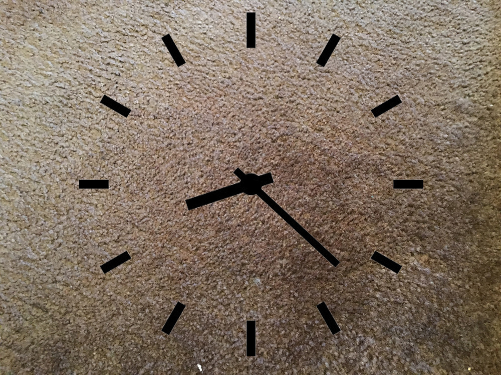 Face of a clock superimposed over carpet.