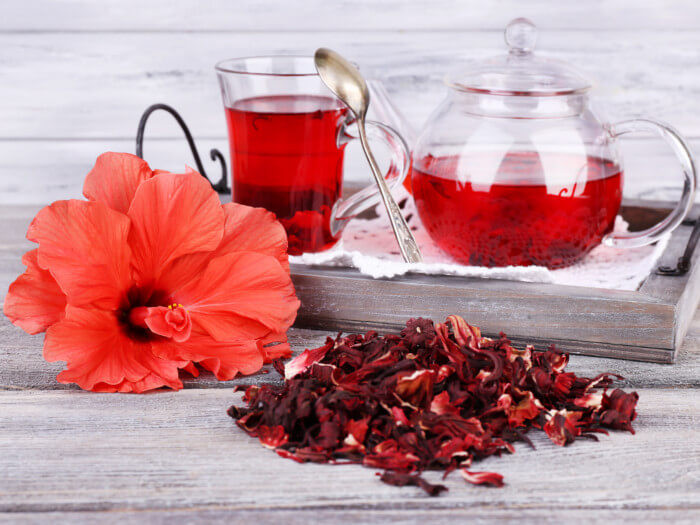 a cup and a pot of hibiscus tea in the back, hibiscus flower fresh and dried in the front