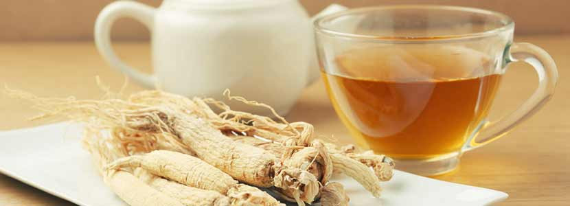 Ginseng root in a plat and a cup of ginseng tea beside